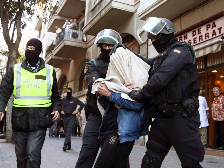 Uno de los tres detenidos sale custodiado por agentes de la benemérita en la calle Marina de Barcelona.