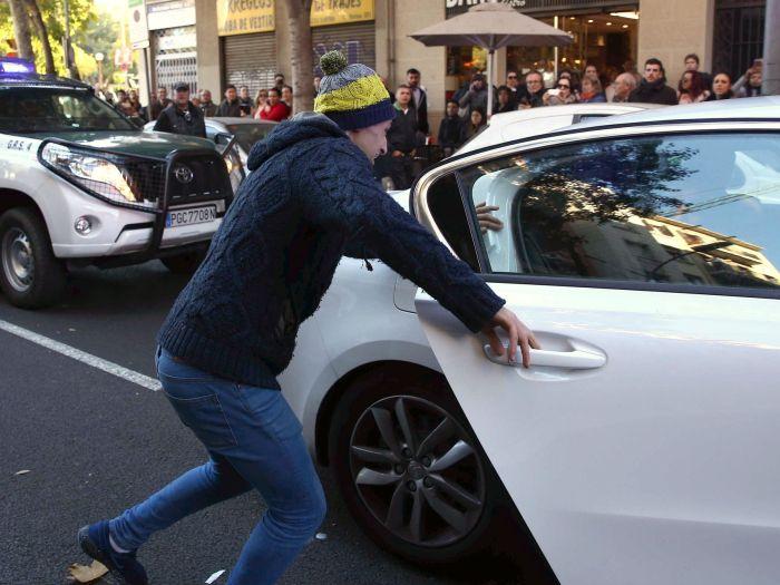 Un familiar de uno de los detenidos intenta sacar al arrestado del coche de los agentes de la Guardia Civil,