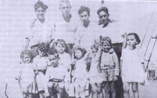 Arriba, Antoñé (bajo una X) posa con varios compañeros y niños.