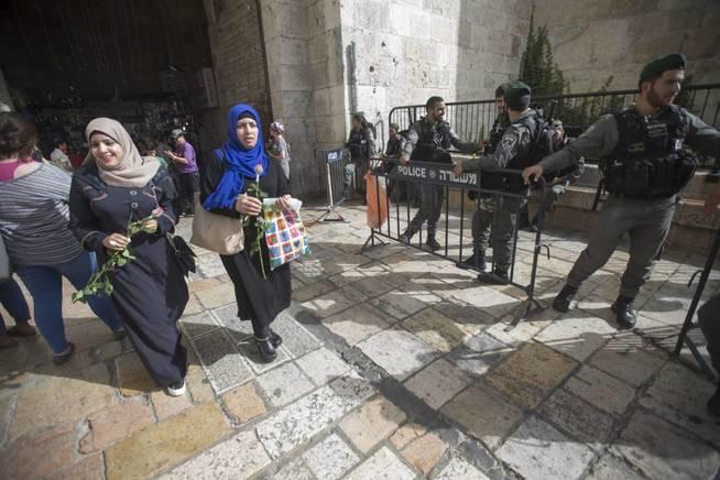 Mujeres palestinas portan rosas como símbolo de la paz durante el 'Día de Jerusalén', el 5 de junio de 2016 (EFE)