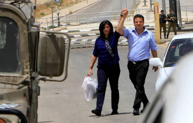 La diputada palestina Khalida Jarrar sostiene la mano del parlamentario árabe-israelí Ayman Odeh tras salir de la cárcel, el 3 de junio de 2016 (Reuters)