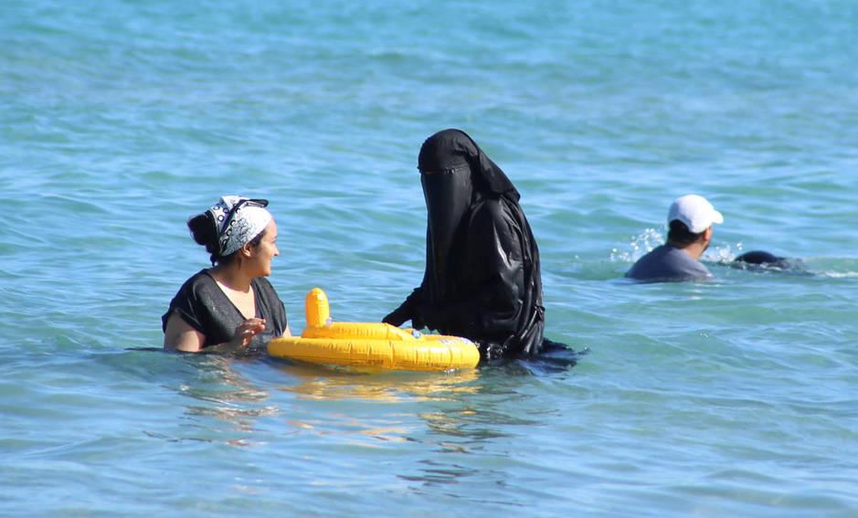 Una mujer se baña con niqab en una playa de Bizerte, Túnez, el 21 de julio de 2016 (Reuters).