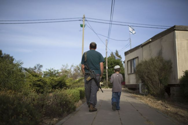 Foto: Un colono judío, junto a su hijo, en el asentamiento de Maon, al sur de Hebrón, en Cisjordania. (Reuters)