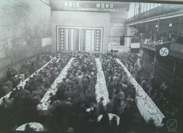 Acto en el Frontón Vitoriano. A la derecha, una esvástica nazi