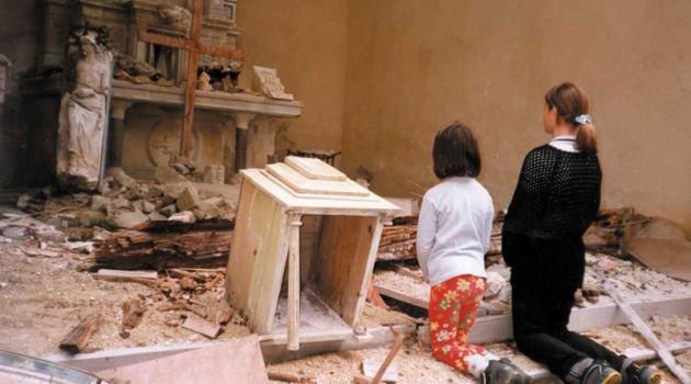 Niñas orando ante ruinas de iglesia
