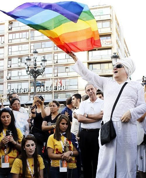 Shangay Lily ondeando una bandera del orgullo gay durante la JMJ