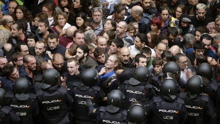 La Policía Nacional trata de evitar que los votantes entre en el colegio electoral.