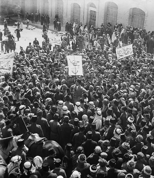 Manifestación árabe en la puerta de Damasco en Jerusalén, 1920. El portavoz es Aref al Aref. Los carteles declaran apoyo a Palestina como parte de Siria.