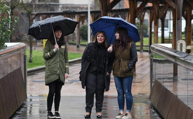 La viuda y las dos hijas de Isaías Carrasco pasean por las calles de Arrasate en una mañana lluviosa.
