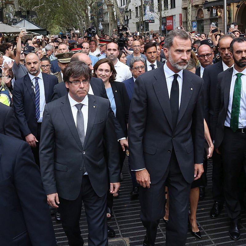 El rey Felipe VI de España (centro), acompañado por el presidente de Cataluña, Carles Puigdemont (izquierda) y la alcaldesa de Barcelona, Ada Colau, se preparan para depositar una ofrenda floral en el lugar de un ataque de camiones dos días antes en La Rambla, que dejó dos muertos. más de 100 heridos, 19 de agosto de 2017. Crédito: Wikimedia Commons.