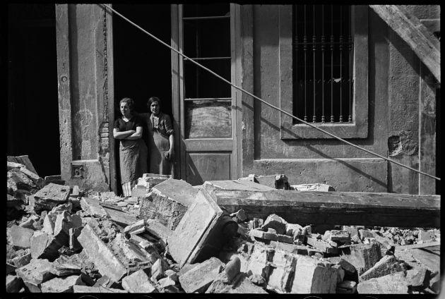 FOTOGALERÍA | Dos mujeres en medio de los escombros en el Poble Sec de Barcelona después de un bombardeo el 14 de marzo de 1937