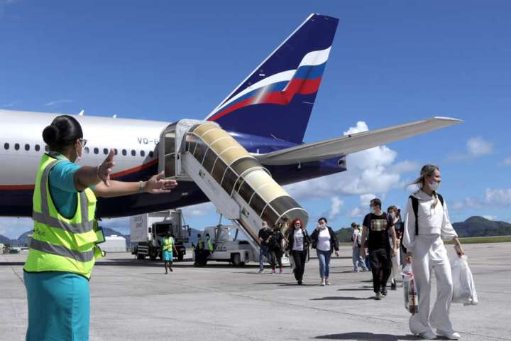 un grupo de personas de pie alrededor de un avión: los pasajeros abandonan un vuelo de Aeroflot desde Moscú en la isla de Mahé en Seychelles el 2 de abril.