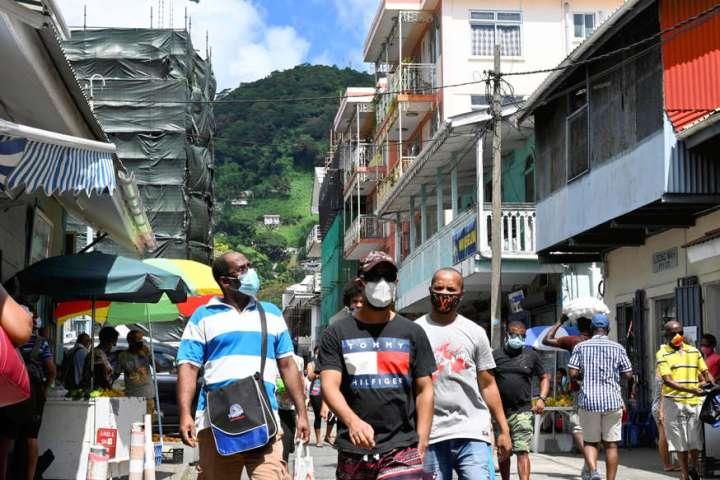 un grupo de personas caminando por una calle: turistas compran en una calle comercial en Victoria, Seychelles, el 2 de abril.
