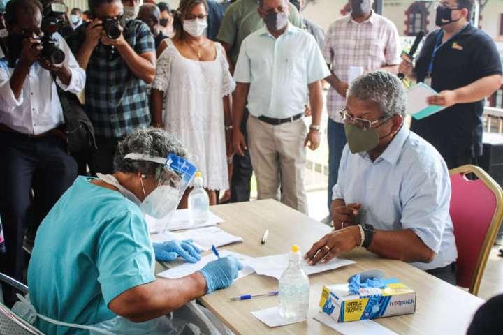 un grupo de personas de pie sobre una tabla de cortar con un pastel: el presidente de Seychelles, Wavel Ramkalawan, responde a las preguntas de un trabajador de la salud antes de recibir la primera dosis de la vacuna contra el coronavirus producida por Sinopharm en el Hospital de Seychelles en Victoria el 10 de enero.